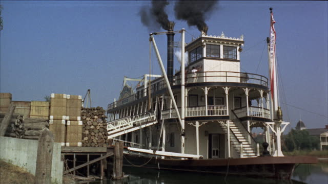 WS Prow over length of riverboat at landing stacks are smoking on it