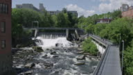 Public river dam and walkway in small city