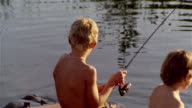 Pull back from rear view of two young boys fishing on wooden raft floating in pond