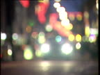 Pull focus from blurry Christmas lights to busy Oxford Street with black cab moving towards camera London