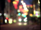 Pull focus from blurry Christmas lights to busy Oxford Street with traffic and shoppers London
