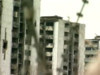 Pull focus from ruined apartment blocks to razor wire Sarajevo 1994