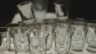 Pull focus on a stack of glass shot glasses.