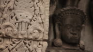 Pull focus onto stone carvings decorating the Angkor Wat temple, Cambodia.