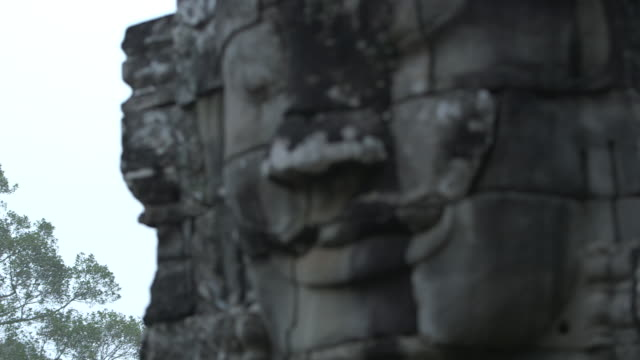 Pull focus shot on a large stone face, decorating the exterior of the Bayon temple at Angkor.