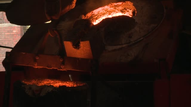 A pulley slowly tips molten steel inside a metal bucket. Available in HD.
