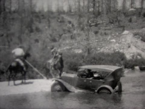 1927 pulling old car across river with two horses