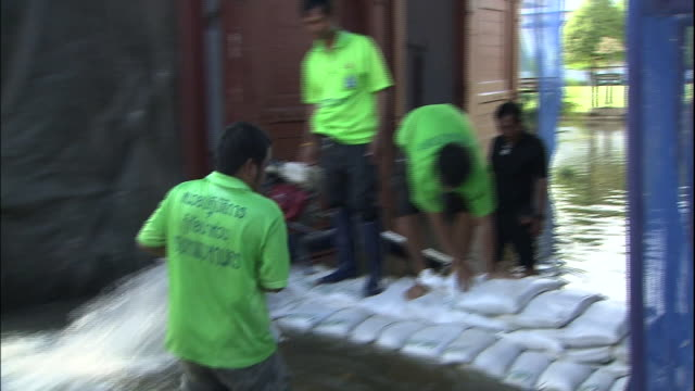 A pump clears flood water while Thailanders stack sandbags