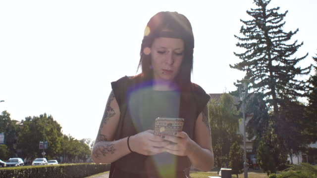 Punk girl typing a message while walking in city