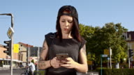 Punk girl using a smartphone in the city