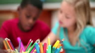 Pupils sitting behind coloring pens