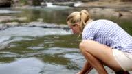 Pura e rinfrescante-donna bere da fiume
