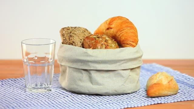 HD Puring Milk in a Glass Beside Bread Basket