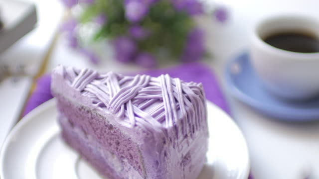 Purple taro cake with coffee on white table at coffee cafe , dolly shot movement