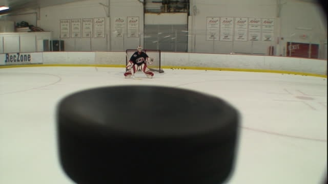 POV push-in - A puck sails through the air above the ice and a goaltender catches it in his glove. / North Carolina, USA