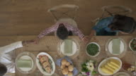 Push-out shot of family members praying before meal