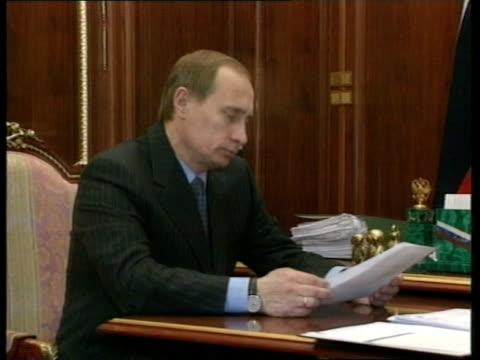 INT Acting Russian President Vladimir Putin shaking Russian envoy to Chechnya Nikolai Koshman Putin Koshman sitting at desk EXT i/c
