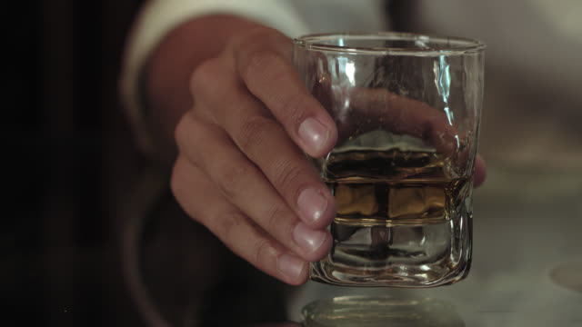 putting back a glass with scotch bourbon single malt whiskey onto a reflecting glass table