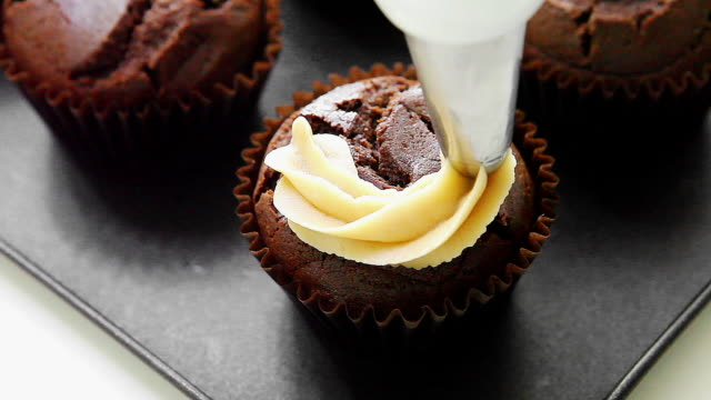 Putting buttercream icing on the chocolate cupcake (Process of making chocolate spread cupcakes)