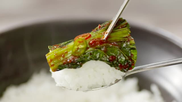 Putting Gat (leaf mustard) Kimchi (Popular traditional side dish in Korea) on top of the rice