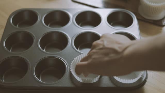 putting-muffin Fällen in Backen tin