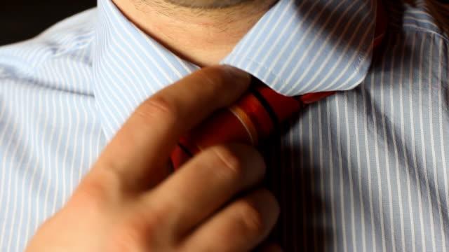 putting on elegant tie