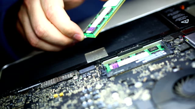 Putting RAM memory chip into laptop.