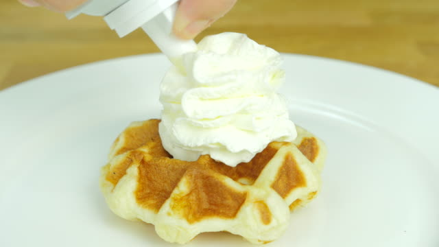 putting whipping cream and strawberry on top of the waffle. Front view.
