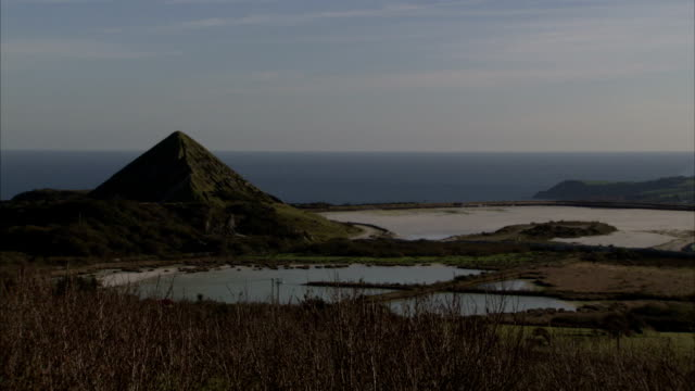 A pyramid of earth created by china clay pit works on horizon overlooking sea, Cornwall. Available in HD.