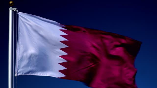 4K: Katar Flagge am Fahnenmast vor blauem Himmel im Freien (Katar)