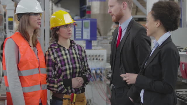 Quality inspectors talking to workers in a factory