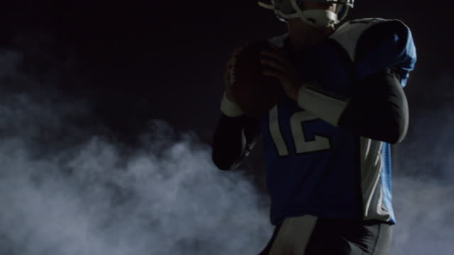 MS SLO MO. Quarterback backs into frame and throws strong pass under stadium lights in professional football game.
