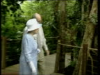 Queen along onto walkway to meet aboriginal guide during tour of rainforest Queen towards with guide CMS Philip towards