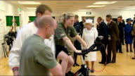 Queen and Duke visit to Headley Court / interiors Patients exercising on mats on floor / Queen being shown equipment and watching soldiers doing...