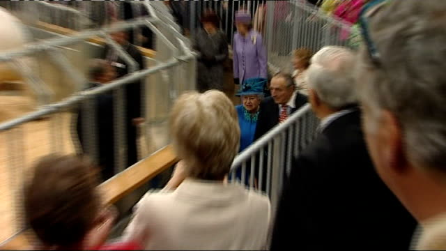 visit to Welshpool livestock market People in auction room applauding Queen Elizabeth II into auction room TRACK behind Queen as she walks past...