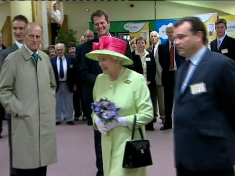 Queen and Prince Philip visit organic dairy products factory Queen and Duke of Edinburgh applauded as entering room / Duke of Edinburgh signing...