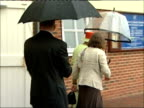 Queen and Prince Philip visit organic dairy products factory Rain falling into puddle / Queen along under umbrella to cheers