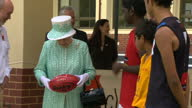 Queen at Aboriginal College Exterior shots Queen is presented with AFL football and is then introduced to female basketball team Queen Elizabeth II...