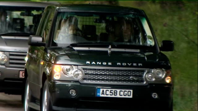 Balmoral EXT Motorcade along road with Range Rover being driven by Queen Elizabeth II and cars turning right