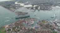 HMS Queen Elizabeth arrives in Portsmouth AIR VIEW / AERIAL HMS Queen Elizabeth in Portsmouth Harbour AIR VIEW helicopters flying past