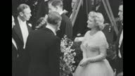 Queen Elizabeth chats with actress Anna Neagle as King George talks to actor George Murphy in the background / the King and Queen continue to greet...