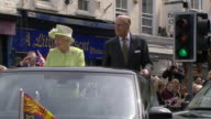 Queen Elizabeth II and the Duke of Edinburgh waving to crowds from a convertible car on the Queen's 90th birthday
