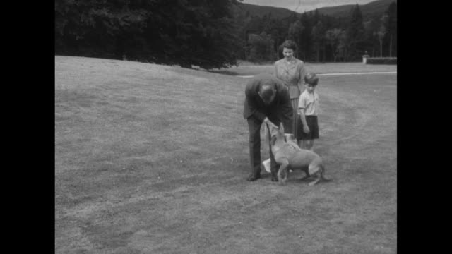 Queen Elizabeth II Princess Anne Prince Charles and Philip Duke of Edinburgh play with dog on grounds of Balmoral Castle a corgi strolls in the...