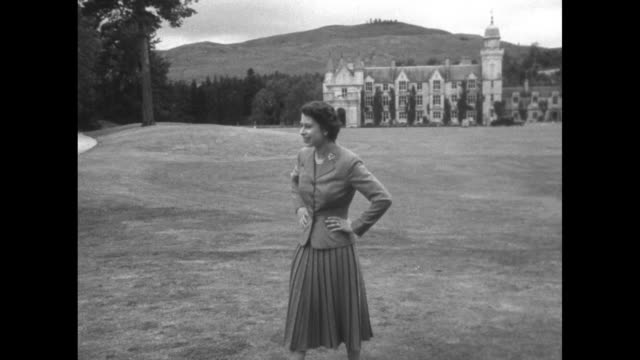 Queen Elizabeth II stands on grounds of Balmoral Castle with Castle standing in background / Queen walks with dogs and Prince Charles Princess Anne...