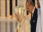 Queen Elizabeth II wearing a headscarf walks alongside Prince Philip whilst on a royal visit to Abu Dhabi
