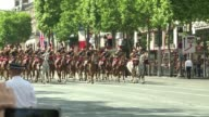 Queen Elizabeth is driven down the Champs Elysees after participating in a ceremony at the Arc de Triomphe