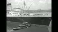 RMS Queen Elizabeth on Hudson River New Jersey coastline in bg / ship docking British Red Ensign flag flying on dock / ship docking / liner with...