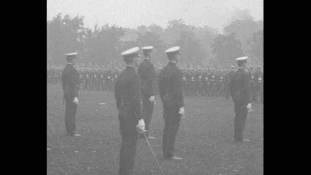 Queen Marie and officials stand under awning / rows of midshipmen march in a field / Queen stands between saluting Admiral Louis Nulton and Prince...