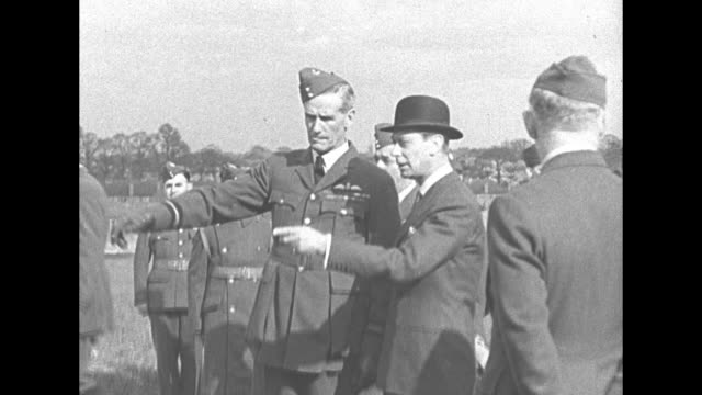GV Queen Mother Elizabeth and King George VI walk in military base surrounded by officers and dignitaries soldiers in battledress stand at attention...
