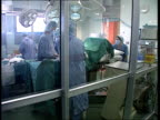 Queen Mother Hip Operation LS Surgeons operating in theatre HEALTH CMS Surgeon masked up with face visor on CLIPREEL OUT
